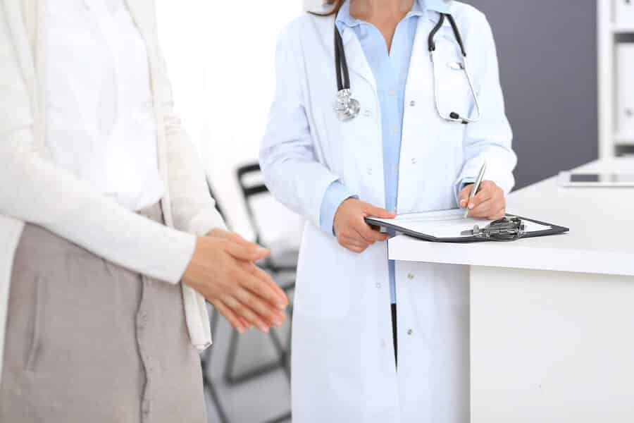 Unknown-Doctor-And-Female-Patient-Discussing-Something-While-S