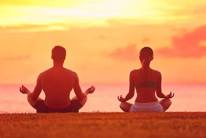 a-man-and-a-woman-sitting-on-a-ground-doing-yoga