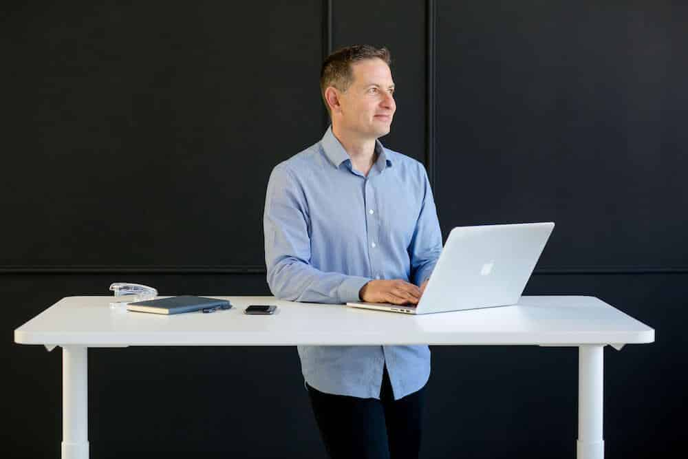 a-man-demonstrating-how-to-use-a-sit-stand-desk