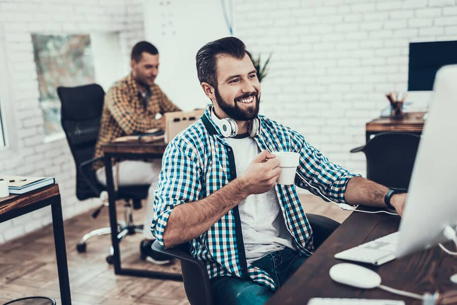 Smiling Bearded Man Sitting on Chair in Office. Didital Device on Desk. Modern Office, Black Chair. Man with Unshaved Face. Work in Office Concept. Young Worker. Man in White Room. White Gadget.