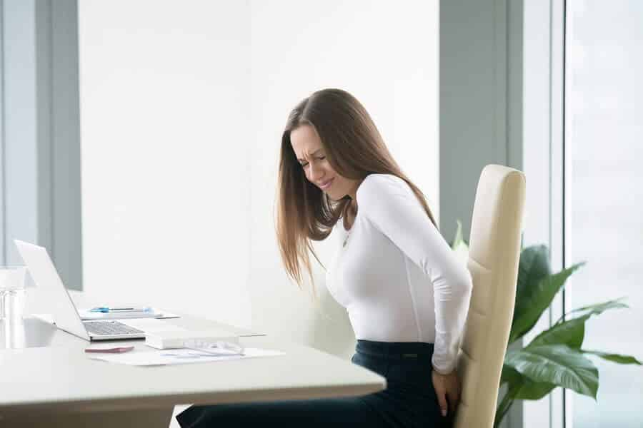 a-woman-sitting-on-a-white-chair-while-holding-her-lower-back-due-to-aching
