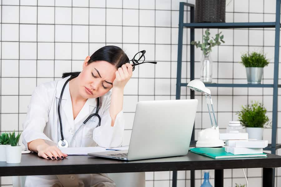 Closeup portrait sad unhappy health care professional with headache stressed sleepy holding cup of coffee. Nurse doctor with migraine overworked overstressed.Needs sit-stand desk