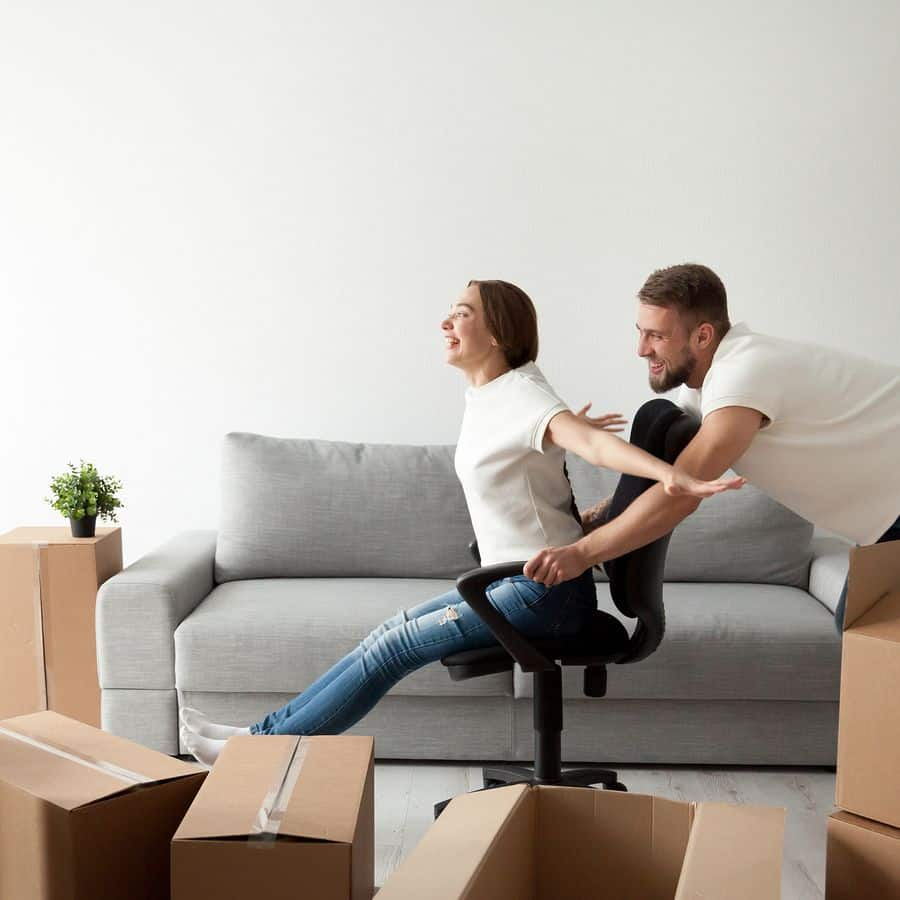 a man and woman happily play with each other using ergonomic office chair