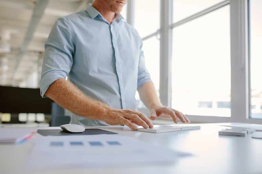 a man using a white ergonomic standing desk